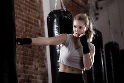 Horizontal view of girl training kick boxing