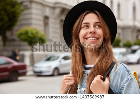 Horizontal view of glad smiling female pedestrian strolls across streets, looks away happily, wears fashionable hat, poses over urban setting with transport, spends weekend discovering new sights #1407569987