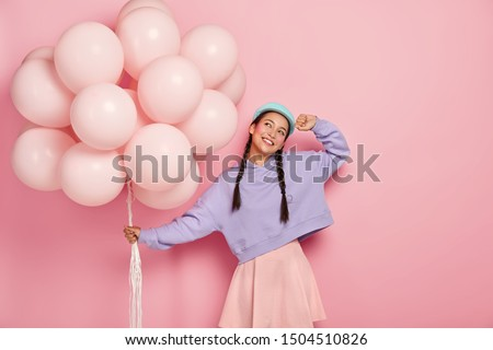 Horizontal view of happy young Asian woman with two pigtails, dreams about awesome holiday, carries bunch of air balloons, imagines lovely moment of celebration, isolated on pink background.