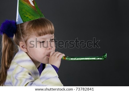 Horizontal view of little girl playfully blowing noisemakers a birthday party