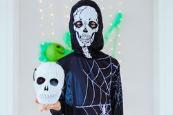Horizontal view of little kid with skeleton spider costume holding a trick or treat Halloween basket shaped as a skull. Halloween costume party for family and children. Seasonal and festive concept.