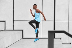 Horizontal view of male athlete dressed in activewear, has cardio running up stairs prepares for jogging on long distance makes steps or jumps high. African American man in t shirt, leggings, trainers