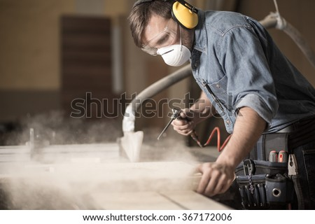 Horizontal view of professionally dressed carpenter varnishing a board