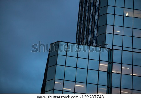 Horizontal view of sky and mirrored building at dusk. Fluorescent office light fixtures can be seen in some windows.