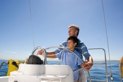 Horizontal waist up shot of a father and son steering a boat on a clear sunny day with copy space.