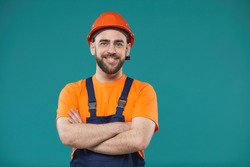 Horizontal waist up studio portrait of cheerful man wearing hardhat and workwear standing with atms crossed looking at camera