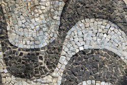 Horizontal wave pattern of cobblestone boulevard sidewalk of Copacabana beach in Rio de Janeiro, Brazil. Close up with texture of real street walkway and sand between the cracks.