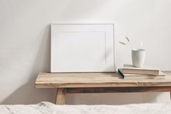 Horizontal white frame mockup on vintage wooden bench, table. Ceramic mug with dry Lagurus ovatus grass and books. White wall background. Scandinavian interior room design. Selective focus.
