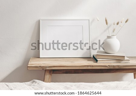 Horizontal white frame mockup on vintage wooden bench, table. Modern white ceramic vase with dry Lagurus ovatus grass and books. White wall background. Scandinavian interior. Selective focus.