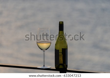 Horizontal white wine glass with bottle on outside deck rail