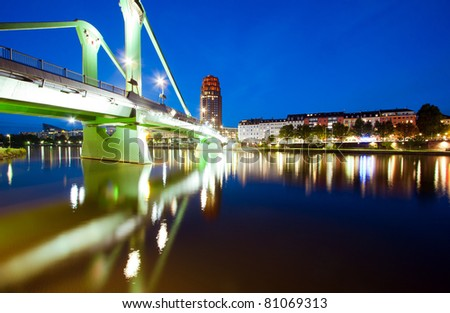 Horizontal wide angle perspective of the green bridge reflecting in the river