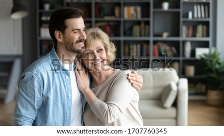 Horizontal wide image inside of cozy living room at home standing hugging middle-aged mother and grown up adult millennial son. Family bonds and values, love care and relatives closest people concept