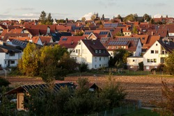Horizontal wide view over an agricultural field, and houses with red roofs in the German village of Malmsheim, in the background. Small town in the southern state of Baden-Württemberg, during daytime