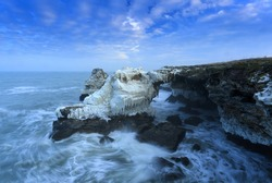 Horizontal winter seascape of frozen rocks near the village of Tyulenovo, Bulgaria with blurry sea and blue sky.