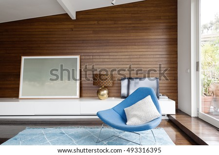 Horizontal wood panelling and blue occasional chair in mid century modern living room #493316395