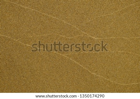 Horizontal zigzag patterns left by waves on a sandy beach, very warm soft indirect light. #1350174290
