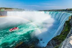 Hornblower Boat Full of Tourists Under Rainbow Sprayed By Horseshoe Waterfall, Niagara Falls, Ontario, Canada