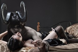 Horned dark-haired devil and cute innocence gothic girl in bed