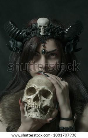 Horned girl posing over dark background with skull