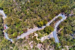 Hornsby heights Galstone road across Berowra creek in narrow and winding path - aerial top down view over gum-tree woods.