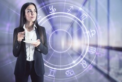Horoscope concept with woman in black suit with cup of coffee on digital screen background with Zodiac signs