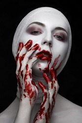 Horrible and Halloween theme: portrait of a young girl model with bandages on her head and blood on her face on a dark background in the studio with bloody hands, bloody make-up