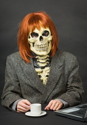 Horrible man - a skeleton with red hair drinking coffee on dark background