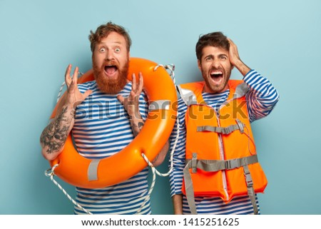 Horrified emotional rescurers work on beach as lifeguards, holds lifebelt, wears orange protective vest, shout from panic as swimmer drowns, needs help, yell oh no. Lifesaving and safe rest concept #1415251625