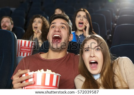 Horrified spectators. Scared young couple screaming terrified while watching a thriller horror movie on their date at the cinema couple love expressive emotional fearful frightened dreadful concept