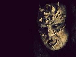 Horror and fantasy concept. Monster with sharp thorns and warts on face. Man with dragon skin and grey beard. Demon head isolated on black. Alien or reptilian makeup, copy space