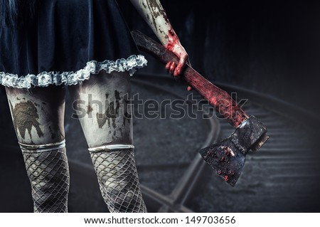 Horror. Dirty woman\'s hand holding a bloody axe outdoor in night forest