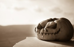 Horror Halloween concept. Close up view of scary dead Halloween pumpkin. Rotten pumpkin head. Selective focus