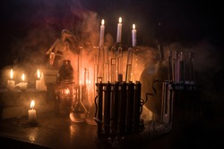 Horror Halloween concept. Magic potions in bottles on wooden table with books and candles. Halloween still-life background with different elements on dark toned foggy background. Selective focus