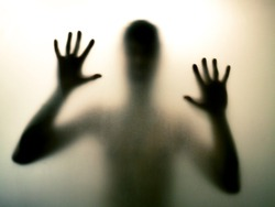 Horror man behind the matte glass in black and white. Blurry hand and body figure abstraction. Halloween background. Murder concept. Criminal concpet.