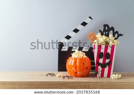 Horror movie night and Halloween party concept with jack o lantern pumpkin,  popcorn and movie clapperboard on wooden table