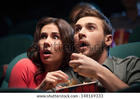 Stock Photo Horror movie. Terrified young couple eating popcorn while watching movie at the cinema