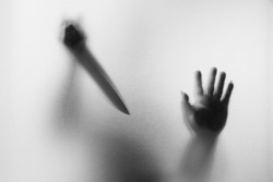 Horror Murderer. Dangerous man behind the frosted glass with a knife on his hand.Halloween background.Black and white picture