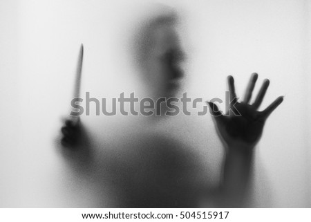 Horror Murderer. Dangerous man behind the frosted glass with a knife on his hand.Halloween background.Black and white picture Stockfoto ©