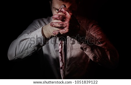 Horror photo of a bloodthirsty killer posing with big bloody kitchen knife holding in both hands.