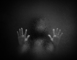 Horror scary shadow of woman behind  glass in black and white. Blurred of  ghost or dead people in darkness. Stressed girl trapped in the room, concept of Halloween or violence against children.