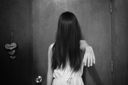 Horror scene of a mysterious girl in white dress. horror woman ghost standing shows hands in an abandoned asian house. Horror scene, Scary background and Halloween concept.