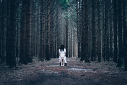 Horror scene of a scary woman: barefoot woman in white dress sitting on the wooden chair  in the middle of a dark, spooky forest