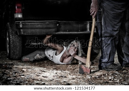 Horror scene of a woman hiding under a truck from a man dragging an Axe