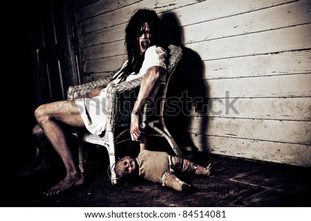 Horror Scene of a Woman Possessed holding a doll sitting in a chair