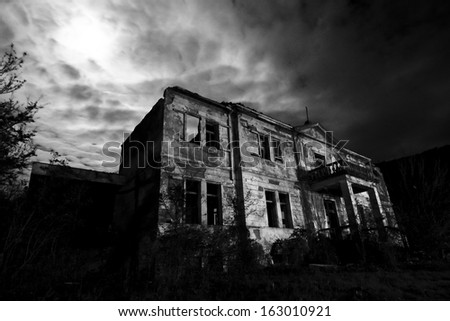 Horror scene of the old grunge building at night over cloudy sky and the moon behind