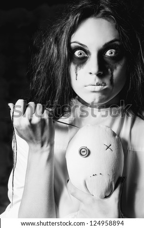 Horror scene: strange crazy girl with moppet doll and needle in hands. Closeup, black and white