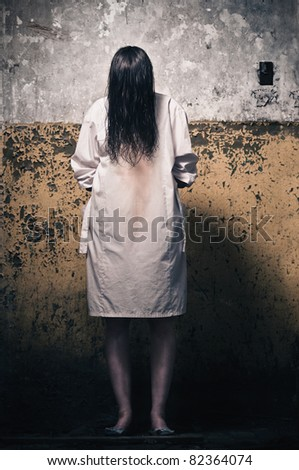 Horror scene with girl in a white coat - stock photo