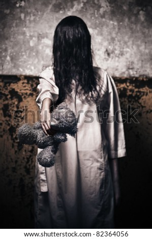 Horror scene with girl in a white robe with a bear in his hand