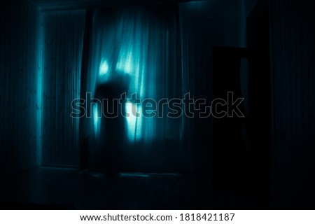 Horror silhouette in window with curtain inside bedroom at night. Horror scene. Halloween concept. Blurred silhouette of ghost Foto stock ©