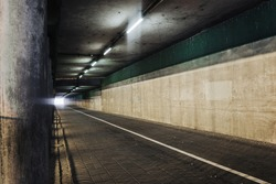 Horror tunnel background. Dark pavement tunnel with bright light at the end. Scary walkway under the bridge. Grunge urban bridge construction.